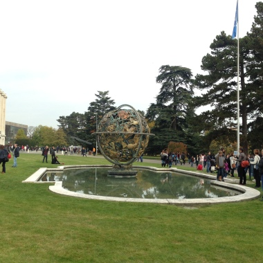 A pond and a sculpture on the lawn in front of the Palais.
